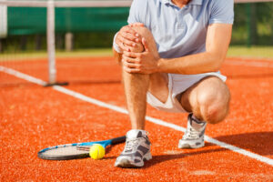 tennis player touching his knee while sitting on the tennis court