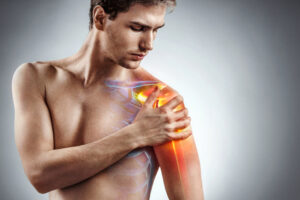 Man holding his injured shoulder that's highlighted in red