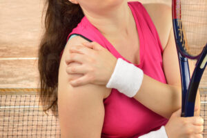 tennis player with a shoulder injury on a clay court